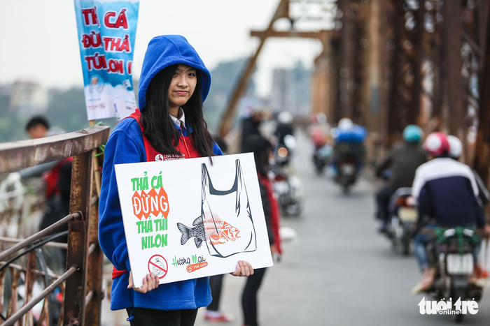 "A member of the Ca Chep (Carp) volunteer group holds a sign saying ""Release carp, not plastic bags"" on Long Bien Bridge."
