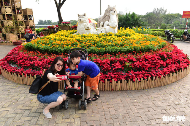 Members of a family enjoy taking photos with a colorful flower display in Phu My Hung residential area in Ho Chi Minh City on February 9, 2018. Photo: Tuoi Tre