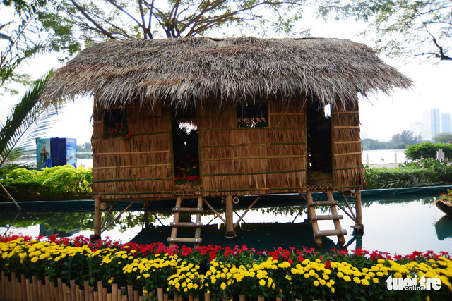 Model of a thatched house is built on a pond in Phu My Hung. Photo: Tuoi Tre