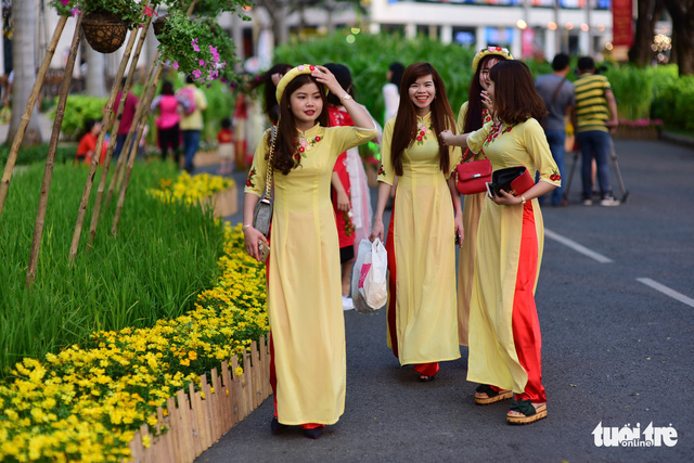 A group of young women wearing Vietnam ao dai takes a walk along a flower-lined street in Phu My Hung. Photo: Tuoi Tre