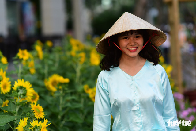 A woman wears a Vietnamese ba ba blouse and a conical hat in Phu My Hung. Photo: Tuoi Tre
