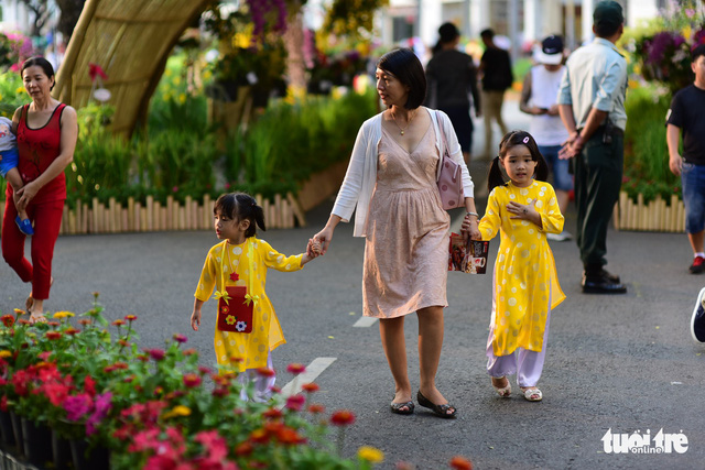 A woman, along with her two little girls, takes a stroll in the flowery Phu My Hung residential area. Photo: Tuoi Tre