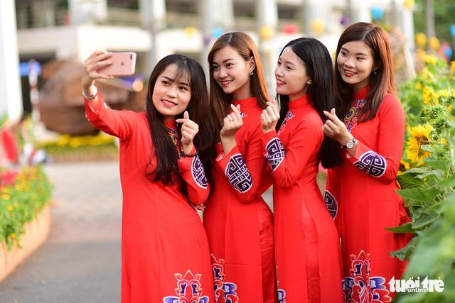 Young women wearing Vietnamese ao dai take a selfie in Phu My Hung. Photo: Tuoi Tre