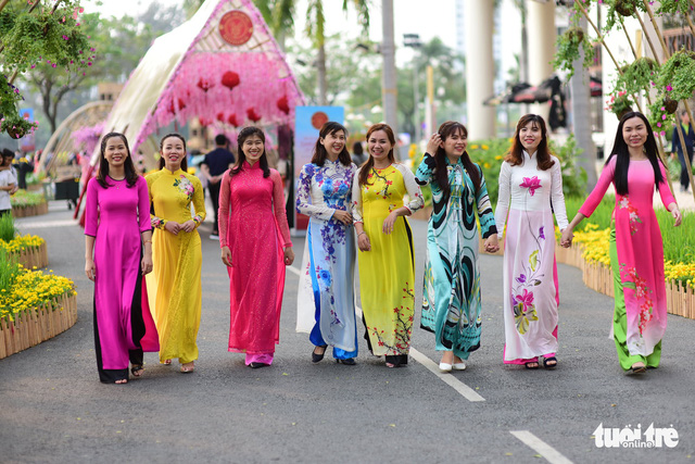 A group of women dressed in Vietnamese ao dai walks leisurely at the flower fair in Phu My Hung Photo: Tuoi Tre