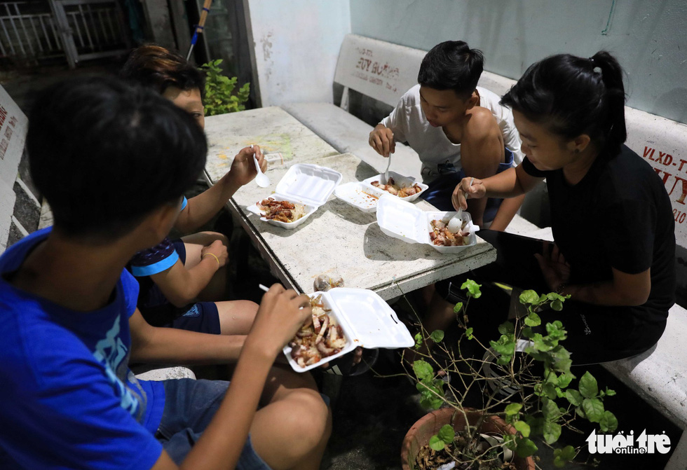 A group of female dancers have dinner after a late night practice session. Photo: Tuoi Tre
