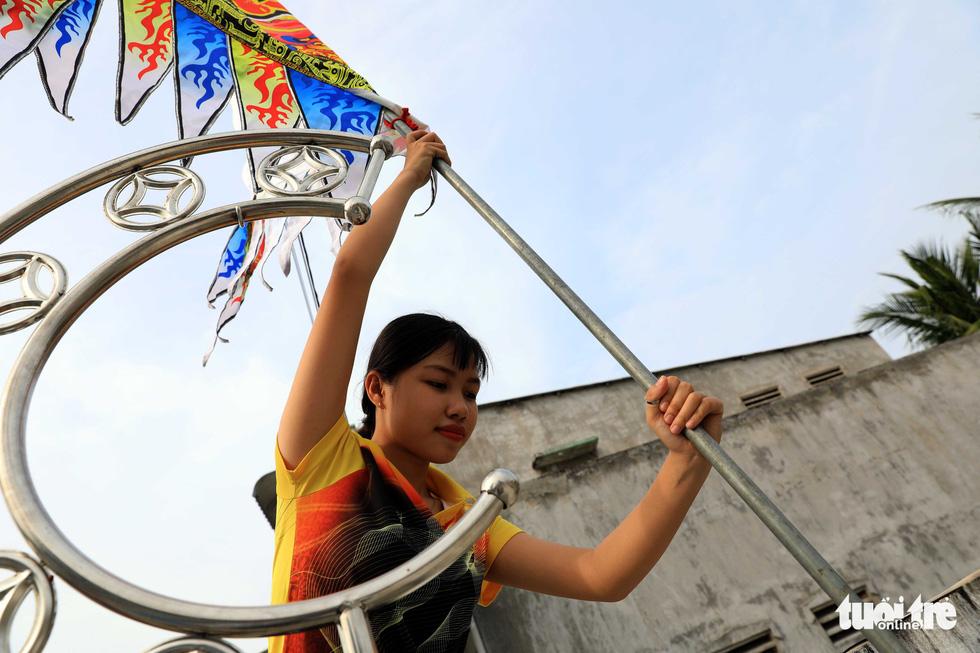 A dancer prepares a flag before a performance. Photo: Tuoi Tre