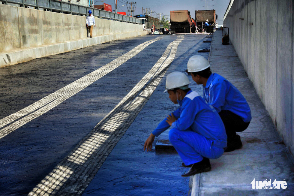 Two workers sit on the curb of the first branch of the An Suong underpass in Ho Chi Minh City. Photo: Tuoi Tre