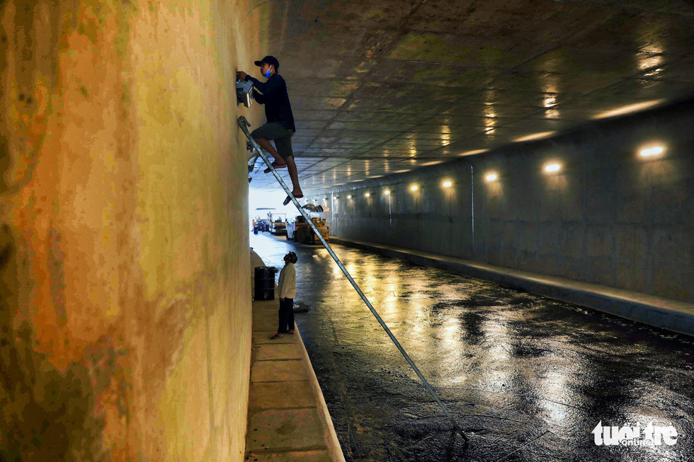 Workers install lighting systems inside the first branch of the An Suong underpass in Ho Chi Minh City. Photo: Tuoi Tre
