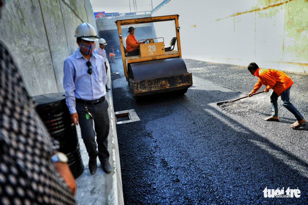 Workers install asphalt on the first branch of the An Suong underpass in Ho Chi Minh City. Photo: Tuoi Tre