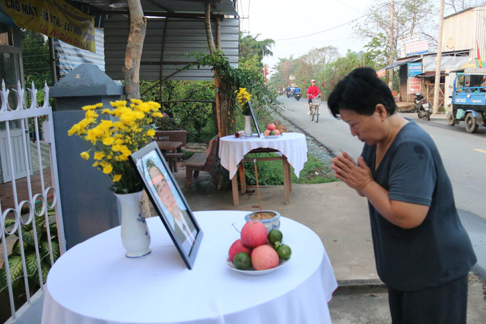 A woman bows to the photo of PM Phan Van Khai displayed on the altar.