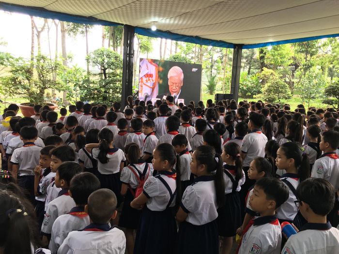 Students of the Tan Thong Elementary School gather at the house of PM Khai to witness the celebration of life.