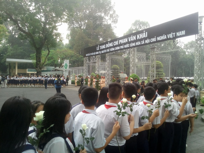 Students holding white roses line up at the entrance of the Reunification Palace.
