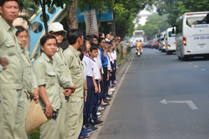 Local residents stand along Phan Thuyc Duyen Street to bid farewell to the late premier.