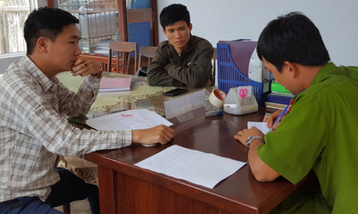 Duong Du Tuan (L) and Chu Ngoai Oai report the incident to police in Nhon Binh Ward in the south-central province of Binh Dinh. Photo: Tuoi Tre