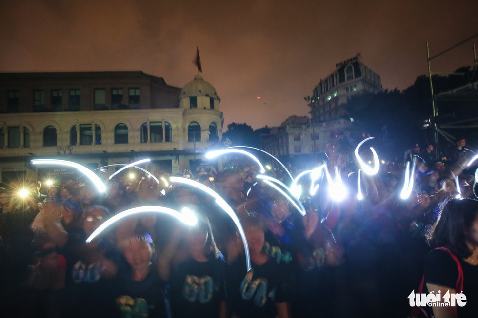 Young people turn on their smartphone flashlights.