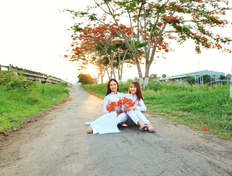 Two young students in ao dai pose under red flamboyant flowers in Dong Thap Province, southern Vietnam. Photo: Tuoi Tre