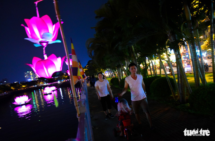 Local people enjoy a walk along the embankment of Nhieu Loc – Thi Nghe Canal in the beautiful light of brightly-colored lanterns. Photo: Tuoi Tre