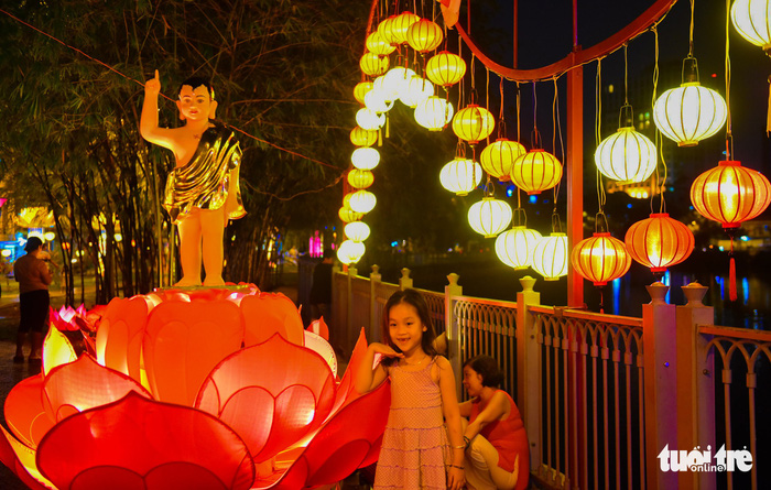 A little girl makes a pose next to the brightly-colored lanterns. Photo: Tuoi Tre