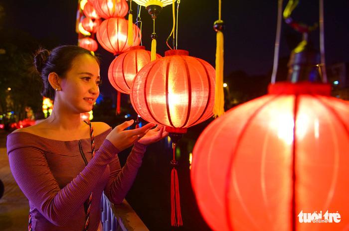 A woman watches a brightly-colored lantern. Photo: Tuoi Tre