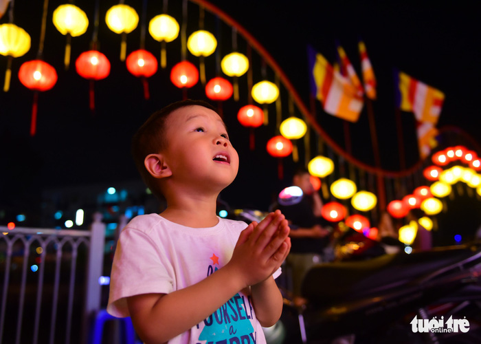 A little boy prays in the background of many brightly-colored lanterns. Photo: Tuoi Tre