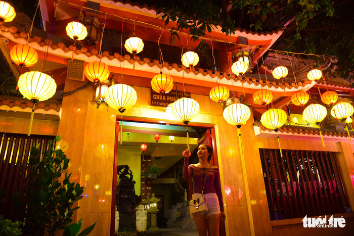 A woman watches the brightly-colored lanterns. Photo: Tuoi Tre
