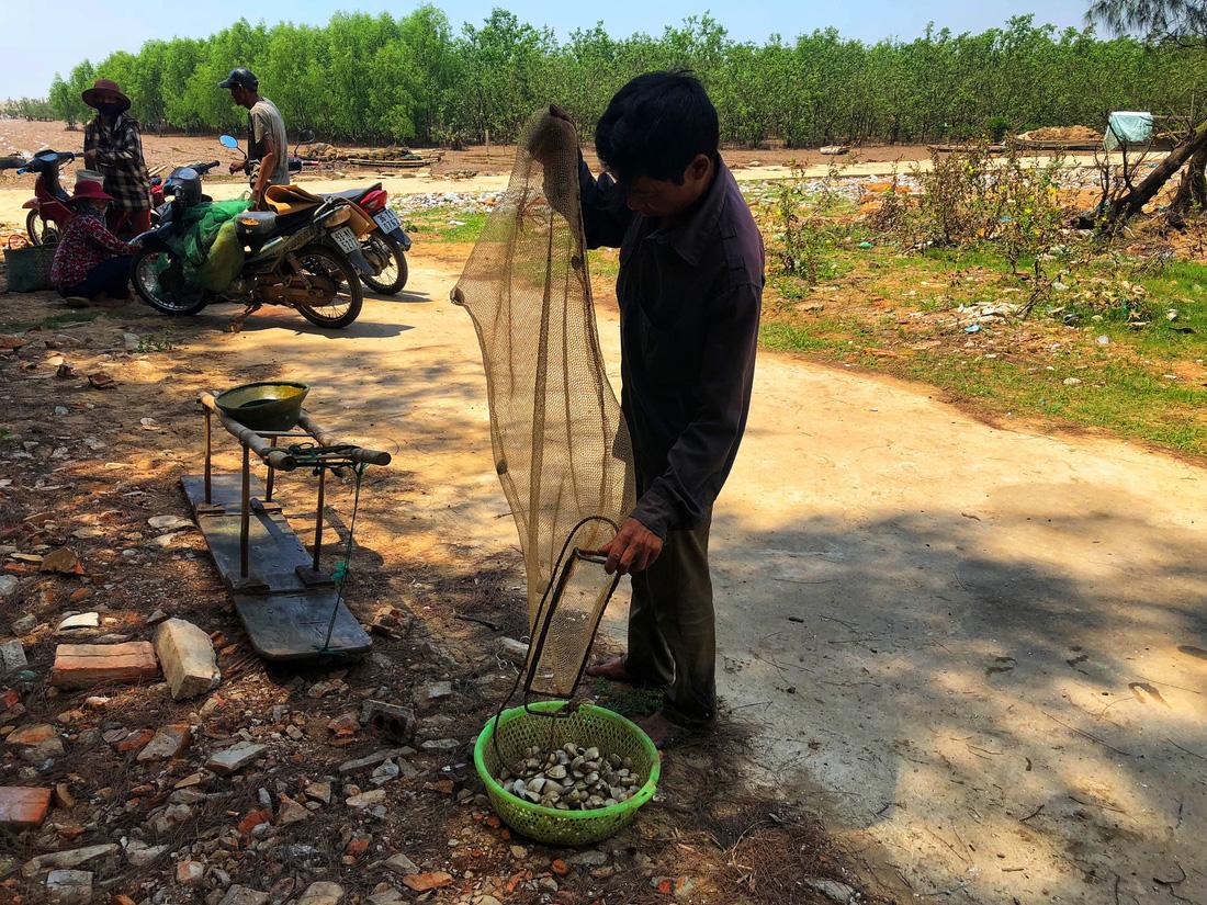 A man collects clams. Photo: Tuoi Tre