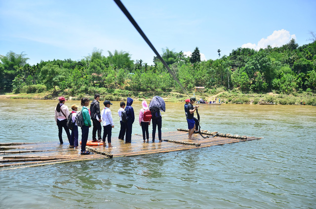 ​Defying currents, students ride bamboo raft to school in central Vietnam