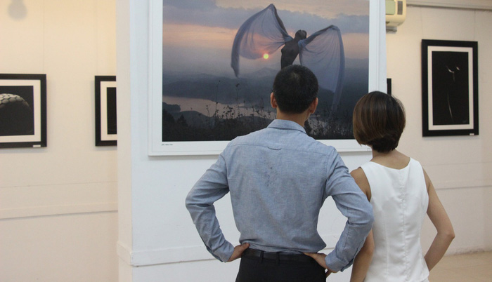 Nhung and her fiancé watch a photo on display at