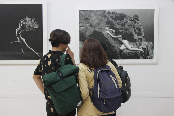 Three college students watch photos on display at
