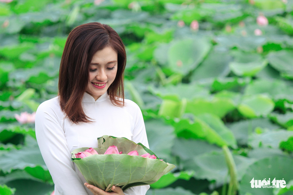 A girl in ao dai poses with lotus flowers in Hanoi. Photo: Tuoi Tre