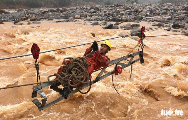 An electrician crosses a stream to restore electricity in Pac Ta Commune, Than Uyen District, located in the northern Vietnamese province of Lai Chau. Photo: Tuoi Tre