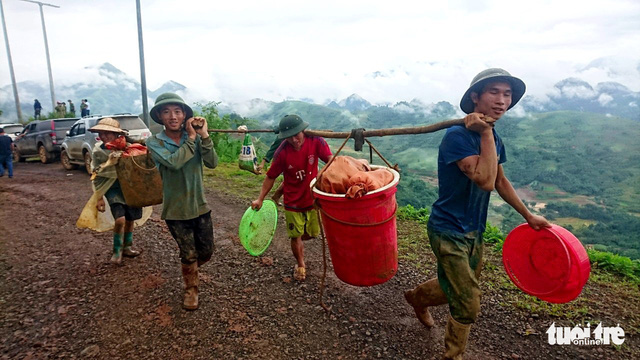 People from Sang Tung Village in Lai Chau carry their belongings to temporary homes after a landslide buried their entire village on June 27.