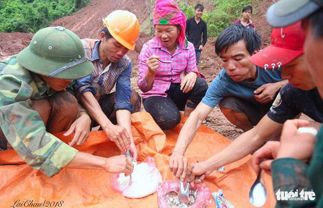 Residents and soldiers share a meal while taking a break from their search for the missing.