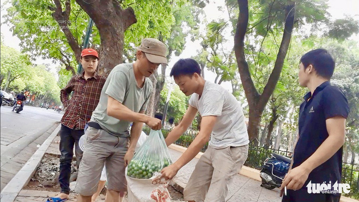 A sau picker sells his fruit on the sidewalk in Hanoi. Photo: Tuoi Tre