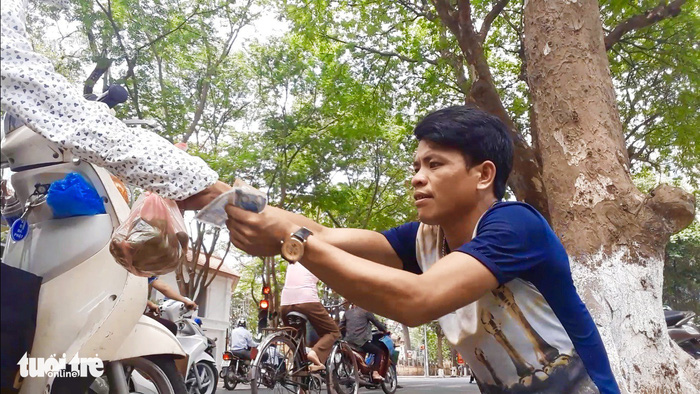 A sau picker sells his fruit on the sidewalk in Hanoi. Photo: Tuoi Tre
