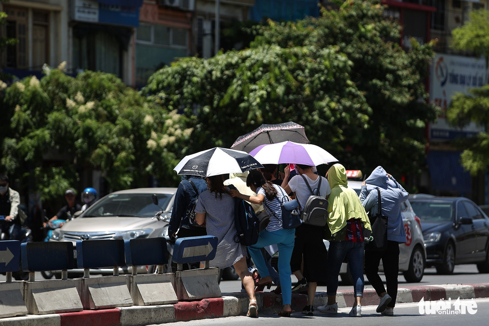 A group of residents cover themselves with jackets and umbrellas as they cross Tay Son Street in Hanoi.