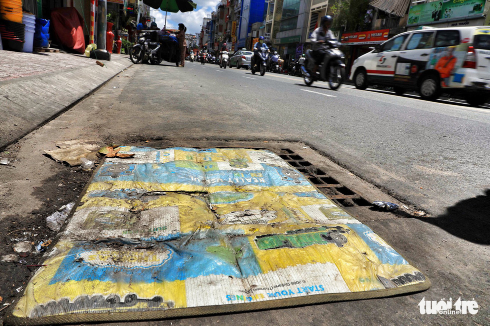 Locals cover up a manhole to block the smell on Phan Dinh Phung Street in Phu Nhuan District.
