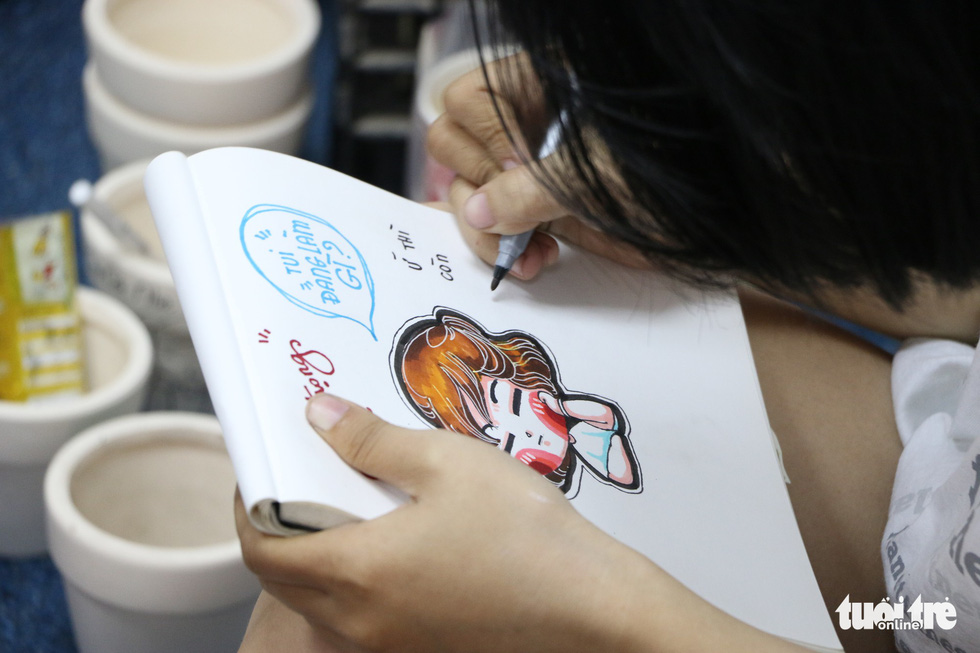 "A staff draws an adorable image in the lovely ""chibi"" art style at Joy Garden. Photo: Tuoi Tre"