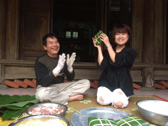 """A tourist takes a photo with her result of wrapping """"banh chung"""" (square glutinous rice cake), an indispensable type of food Vietnamese people often have for Lunar New Year, during a homestay experience in Vietnam associated by Ecohost. Photo: Ecohost"""