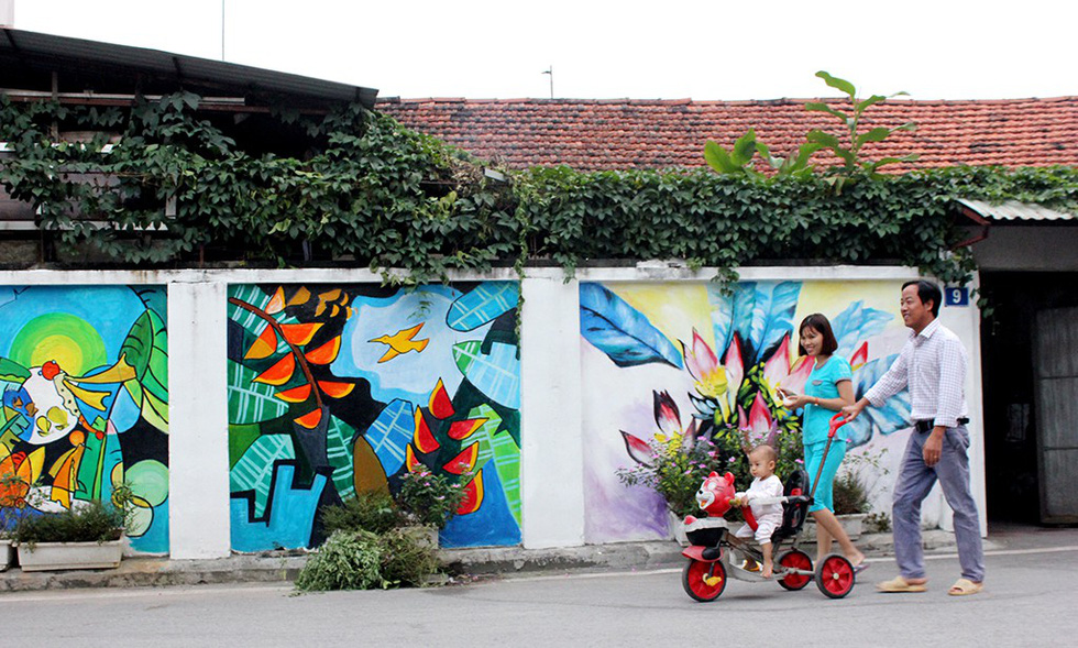 A couple of parents walk their baby along a mural wall in Dong Khe Hamlet of Dan Phuong Village in Dan Phuong District, Hanoi. Photo: Tuoi Tre