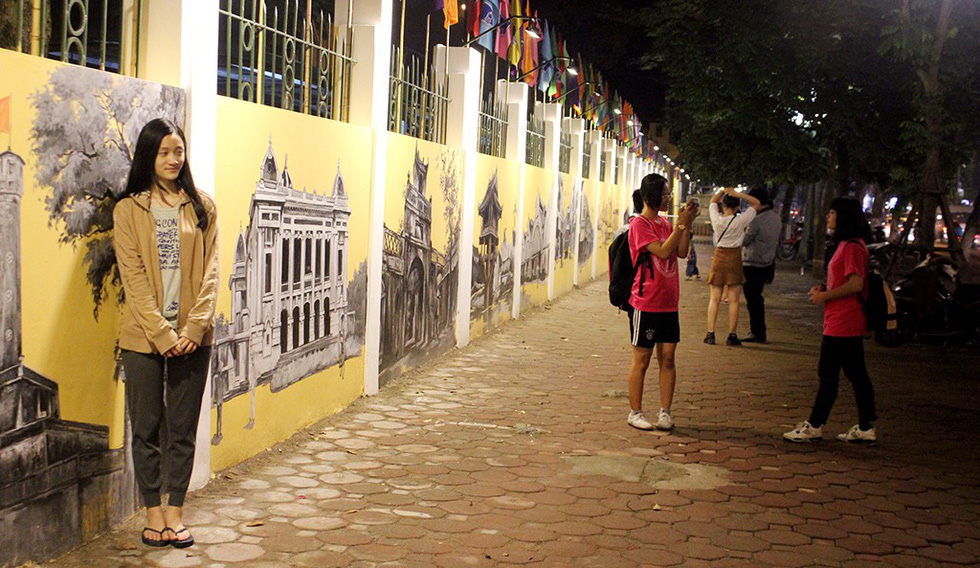 A young girl poses for a photo along the mural wall in Phan Dinh Phung Street in Ba Dinh District, Hanoi. Photo: Tuoi Tre