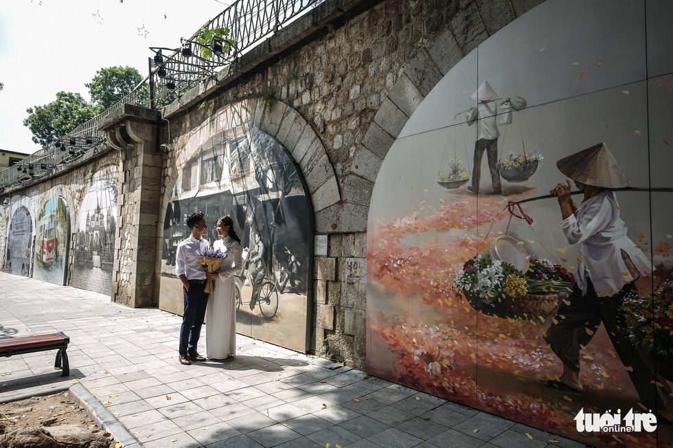 A couple pose for their wedding photos next to amural wall in Phung Hung Street in Hoan Kiem District, Hanoi. Photo: Tuoi Tre