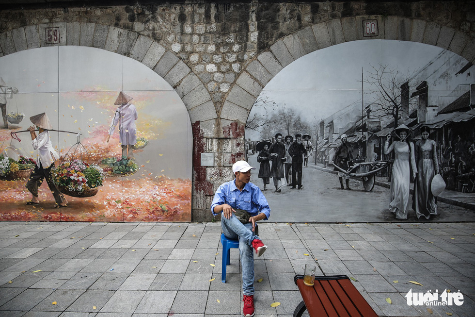 A man sits next to a mural wall in Phung Hung Street in Hoan Kiem District, Hanoi. Photo: Tuoi Tre