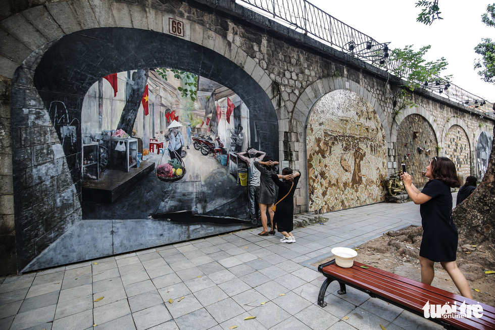 Tourists take photos next to a mural wall in Phung Hung Street in Hoan Kiem District, Hanoi. Photo: Tuoi Tre