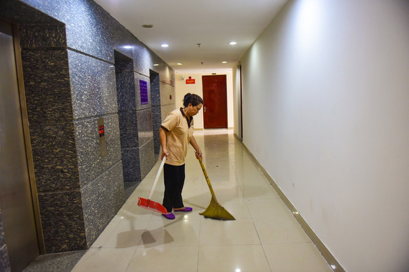 An employee cleans up the hallway of an apartment building. Photo: Tuoi Tre