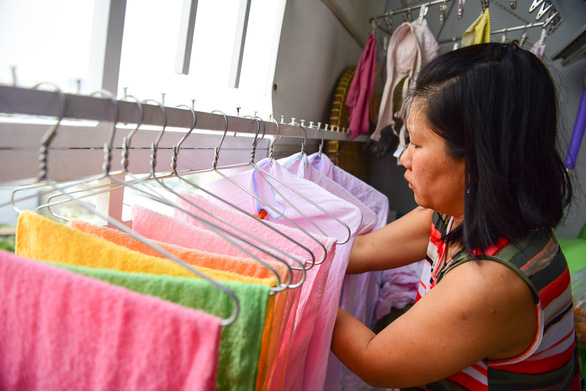 A resident hangs her clothes inside an apartment within the complex. Photo: Tuoi Tre