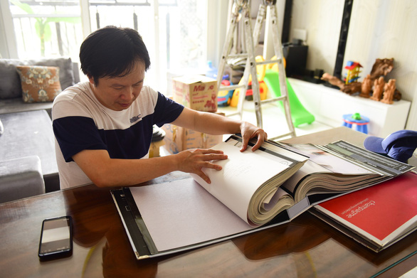 Nguyen Quoc Giang browses for wallpapers to redecorate his home. Photo: Tuoi Tre