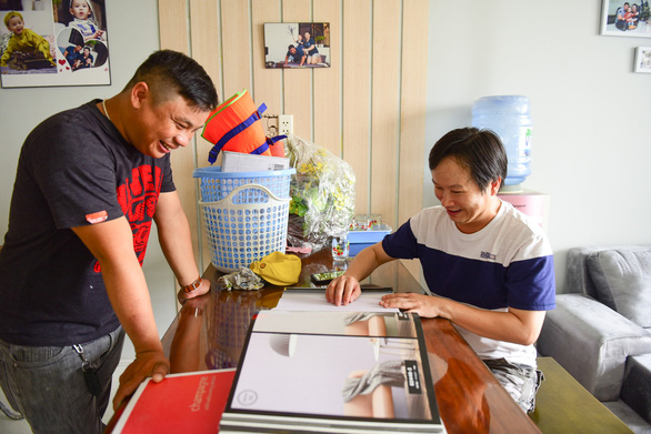 Nguyen Quoc Giang (R) browses for wallpapers to redecorate his home. Photo: Tuoi Tre