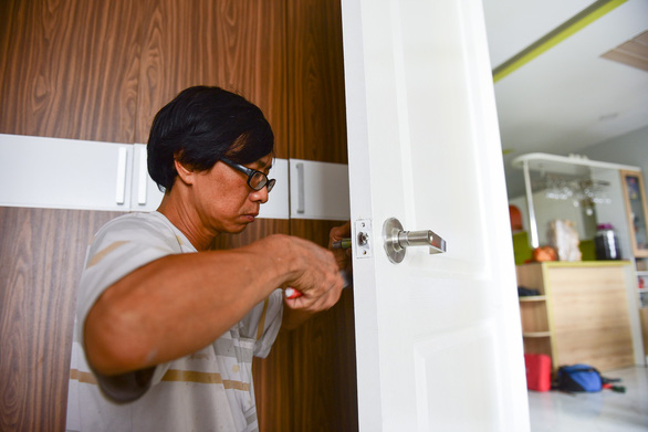 A man fixes a door lock of an apartment. Photo: Tuoi Tre