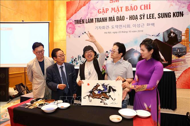 Lee Seong Keun (center) poses with his painting at the press conference on October 22, 2018. Photo: Vietnam News Agency